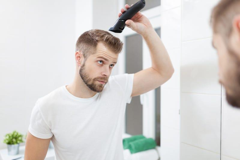 man cutting his own hair