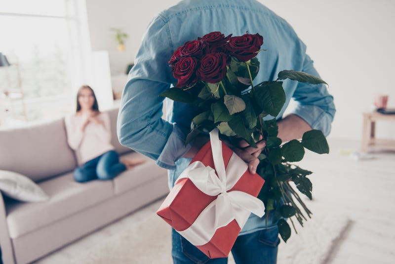 A man holds a wrapped gift and a bouquet of flowers behind his back while a woman waits on a couch in the background