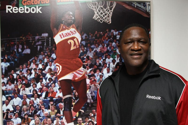 Dominique Wilkins stands in front of a poster of himself.