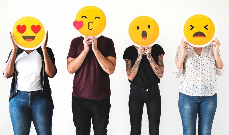 Diverse people holding emojis
