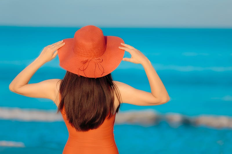 sunbathing woman in hat looking at the sea