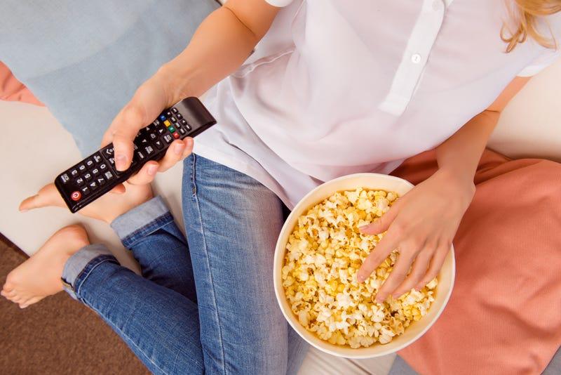 mujer viendo televisión y comiendo popcorn