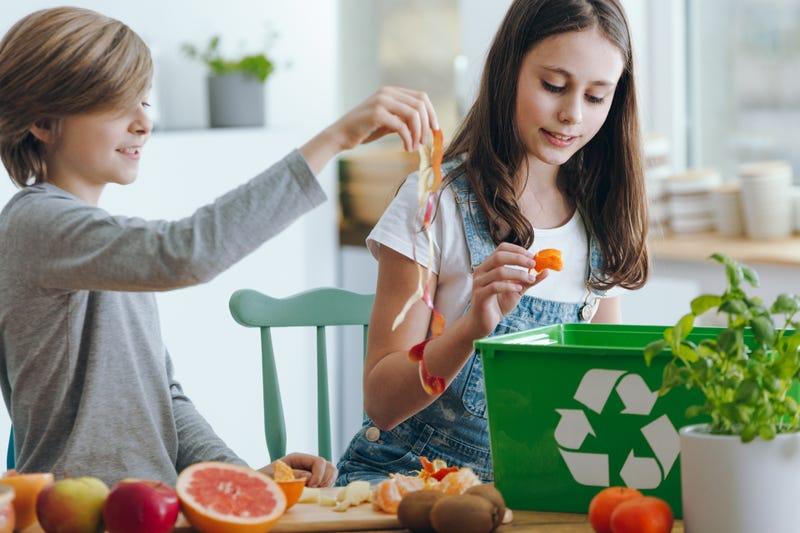 Kids adding food scraps to a compost bin