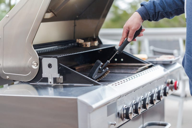 man cleaning grill barbecue