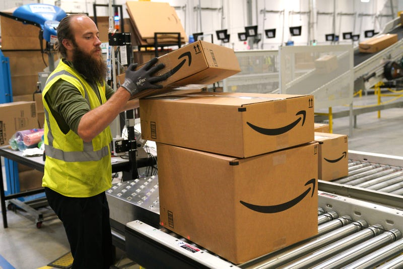 A worker moves packed boxes at the Amazon fullfillment center May 3, 2018 in Aurora, Colorado. The million square foot facility, employing 1,000 fulltime employees, has over 2 million products ready to ship to customers globally.
