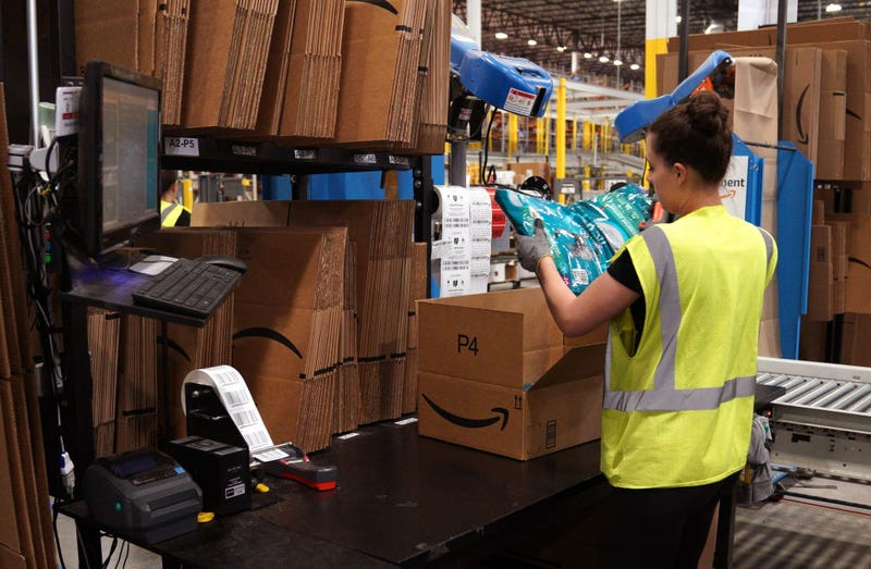 A worker packs cat food at the Amazon fullfillment center May 3, 2018 in Aurora, Colorado.