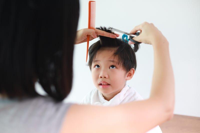 mom cutting son's hair