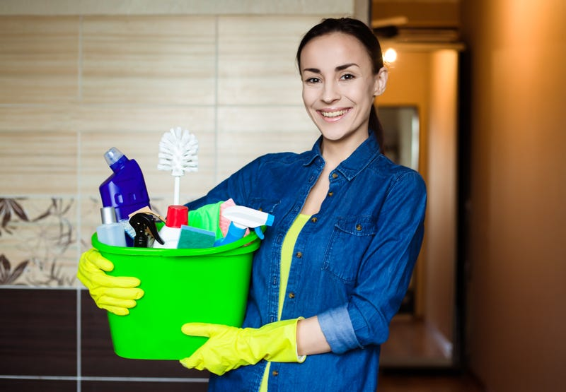 A house cleaner holding a bucket of supplies