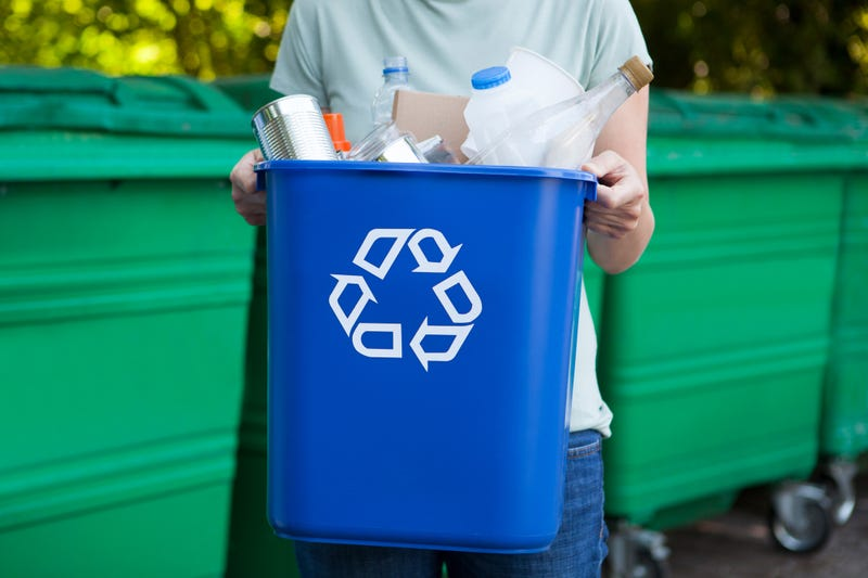 A person holding a recycling bin filled with items