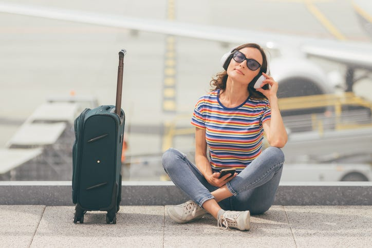 girl with headphones on next to a suitcase