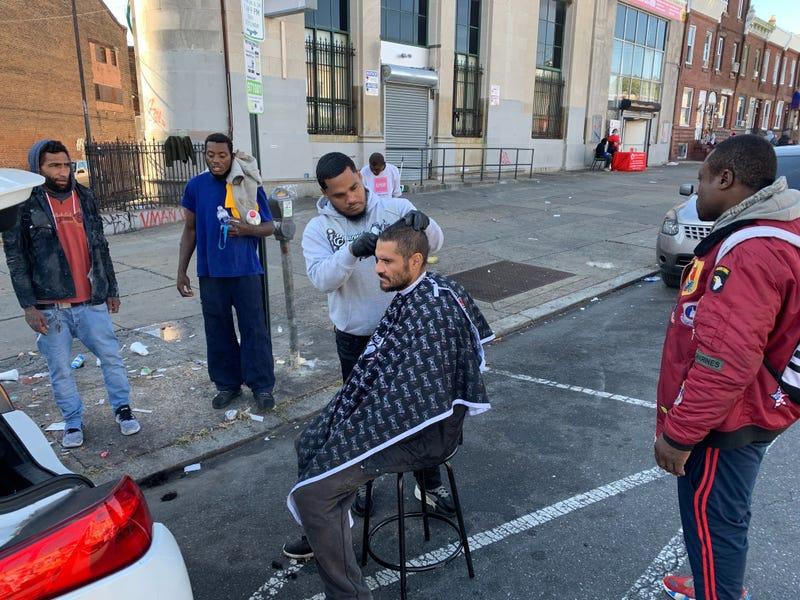Joshua Santiago gives Angel Ramirez a haircut while other men gather to wait their turn.