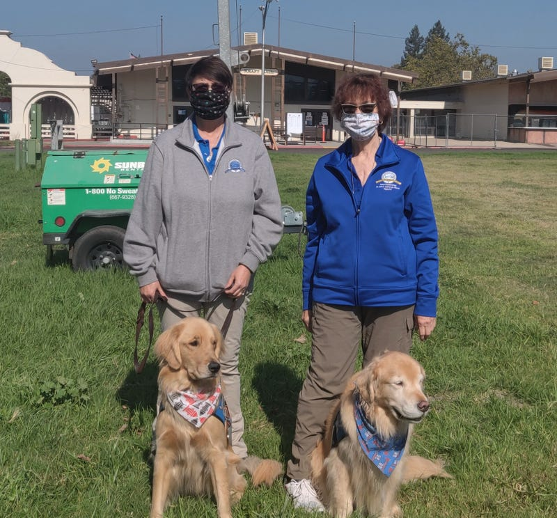 Linda Melsheimer with Micha (left) and Marilyn Hunter with Aaron (right) visiting firefighters at CAL FIRE base camp in Santa Rosa.