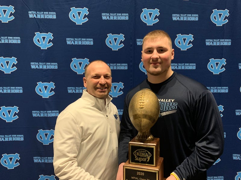 Central Valley head coach Mark Lyons (L) and defensive lineman Sean FitzSimmons (R) pose with Sean's 3A KDKA Radio Super 7 Player of the Year trophy.