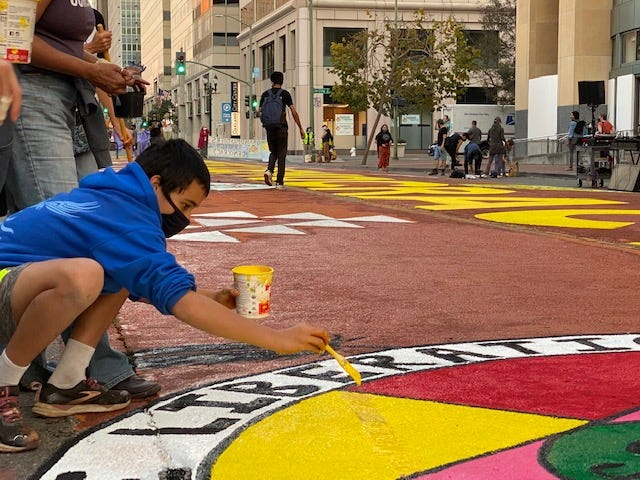 """An activist paints a colorful """"Choose Democracy"""" mural Thursday afternoon in downtown Oakland."""
