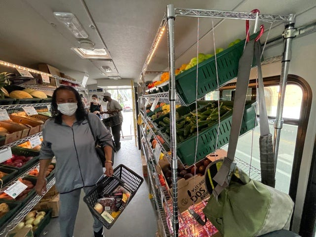 People shopping the Fresh Moves Mobile Market bus.