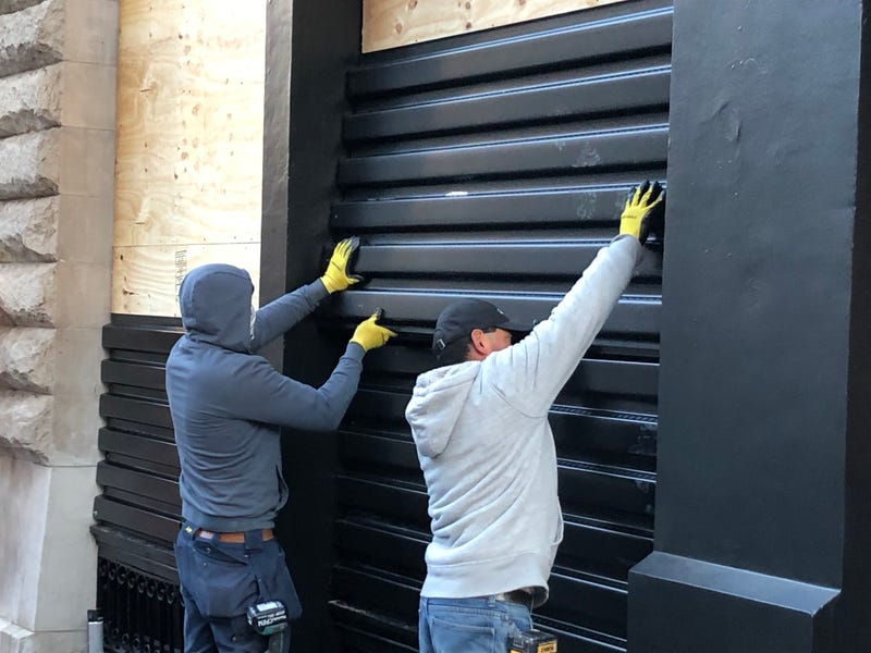 Workers board up Chanel in SoHo on Oct. 31, 2020.