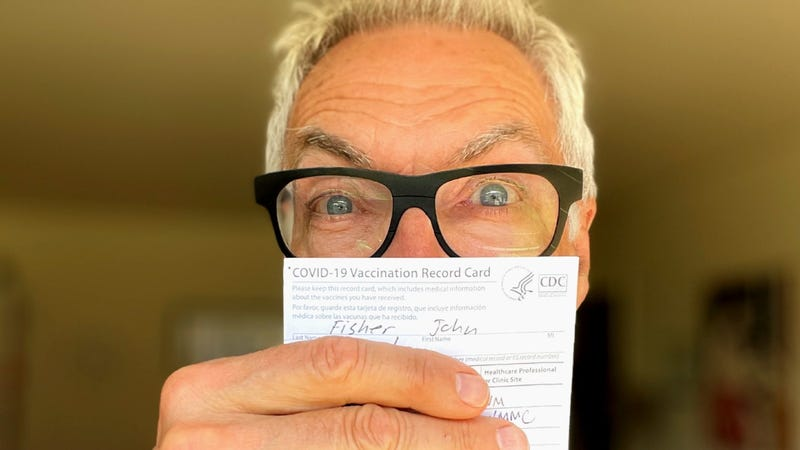 John holding his vaccination card