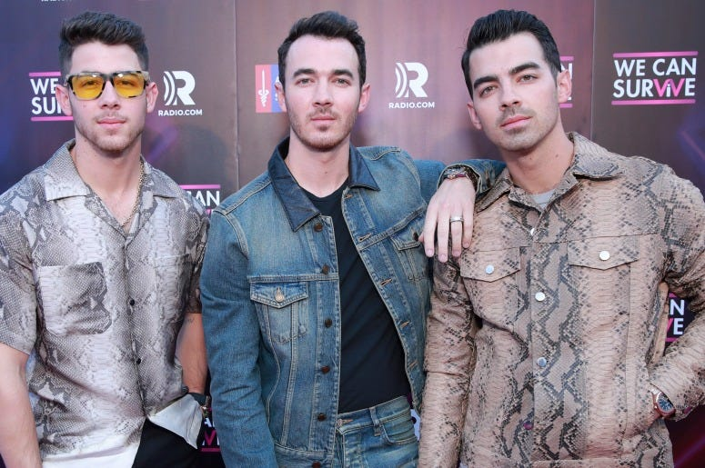 Nick Jonas, Kevin Jonas and Joe Jonas of Jonas Brothers attend the meet and greet during the 7th Annual We Can Survive, presented by AT&T, a RADIO.COM event