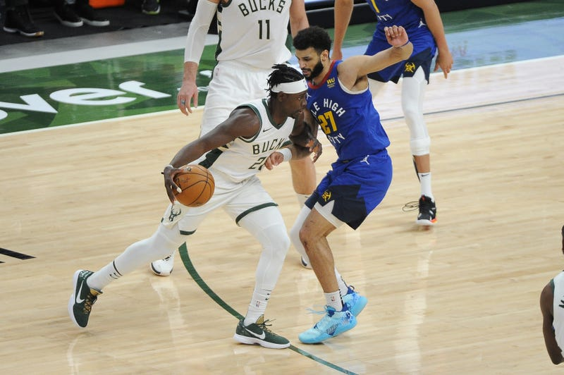 Mar 2, 2021; Milwaukee, Wisconsin, USA; Milwaukee Bucks guard Jrue Holiday (21) dribbles the ball against Denver Nuggets guard Jamal Murray (27) in the second quarter at Fiserv Forum. Mandatory Credit: Michael McLoone-USA TODAY Sports