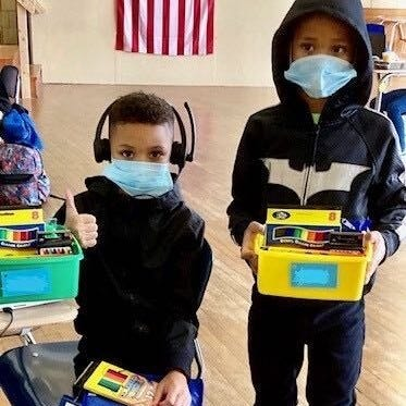 From left: Khamir and Khasim Washington attend virtual school at one of the city's public access centers.