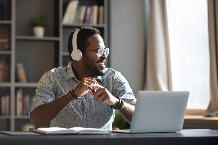 man with headphones on in front of laptop