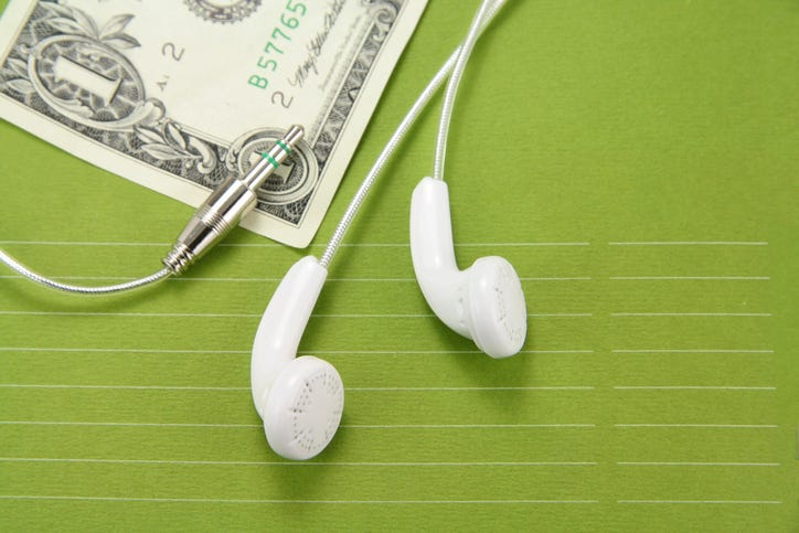 dollar bill with headphones next to it