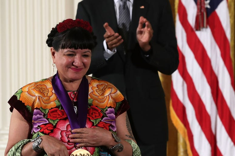 U.S. President Barack Obama (R) presents the National Medal of Arts to author Sandra Cisneros (L) during an East Room ceremony at the White House September 22, 2016 in Washington, DC. President Obama awarded the 2015 National Medal of Arts and the National Humanities Medal to recipients in the annual ceremony.
