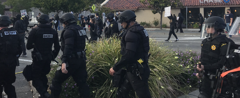 Officers in riot gear following demonstrators in downtown Walnut Creek on Sunday evening.