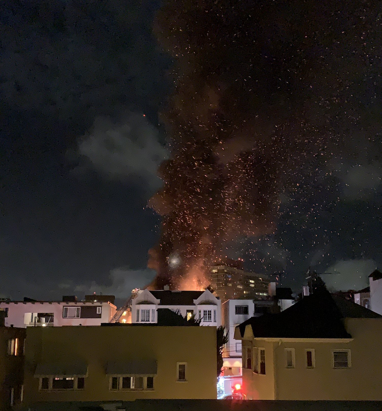 A fire at an apartment building in Oakland on Sunday night seen from a short distance away.