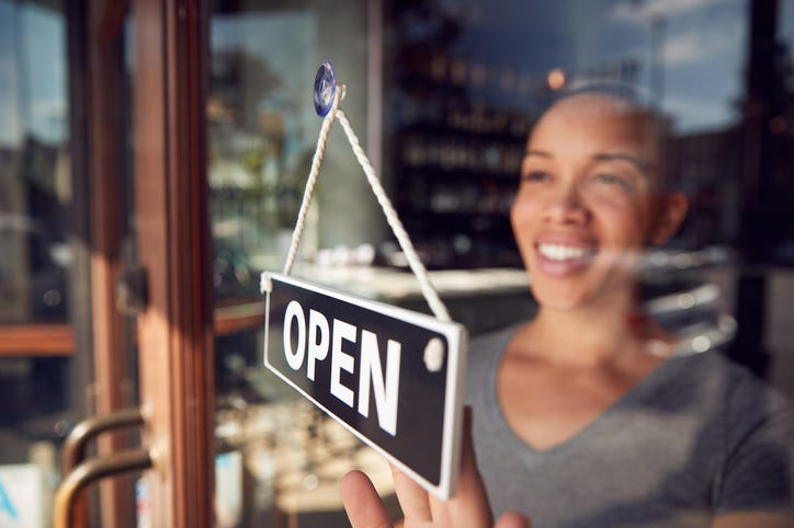 """Black woman turns sign to """"Open"""" at front of small business"""