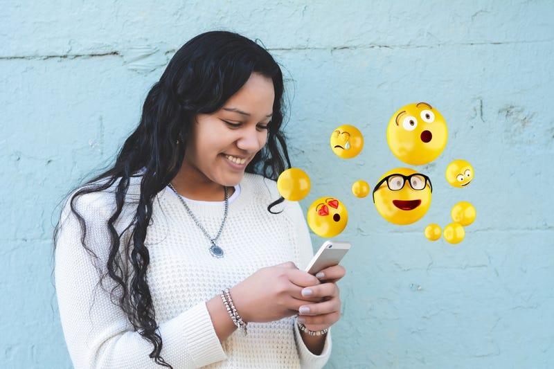 Girl texting using emojis