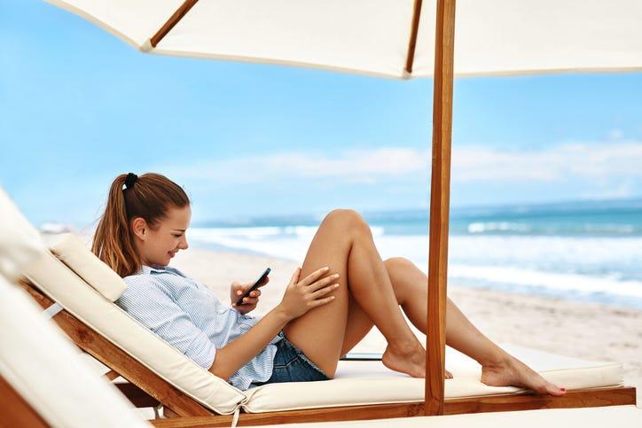 girl texting on the beach