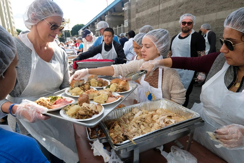 Servers dish out Thanksgiving foods for a charity meal in LA