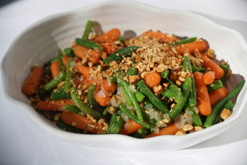 A serving dish filled with green beans, carrots, and chopped nuts