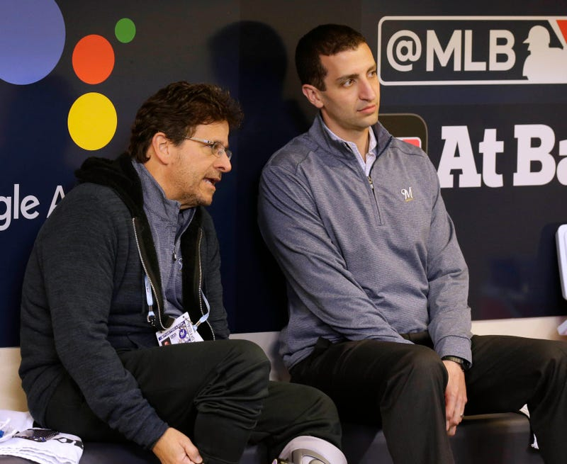 Brewers' GM David Stearns and owner Mark Attanasio chat in the dugout.