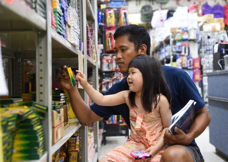 father shops for school supplies with daughter
