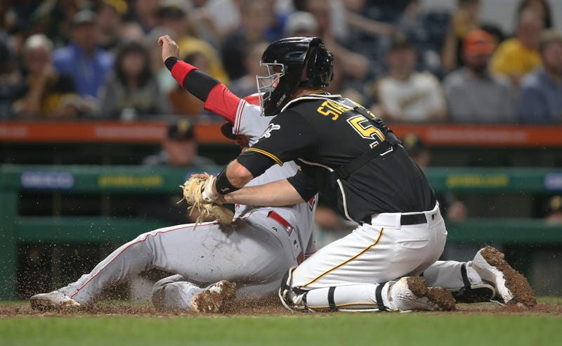 Pittsburgh Pirates catcher Jacob Stallings (58) tags Cincinnati Reds shortstop Jose Iglesias (4) out at home plate