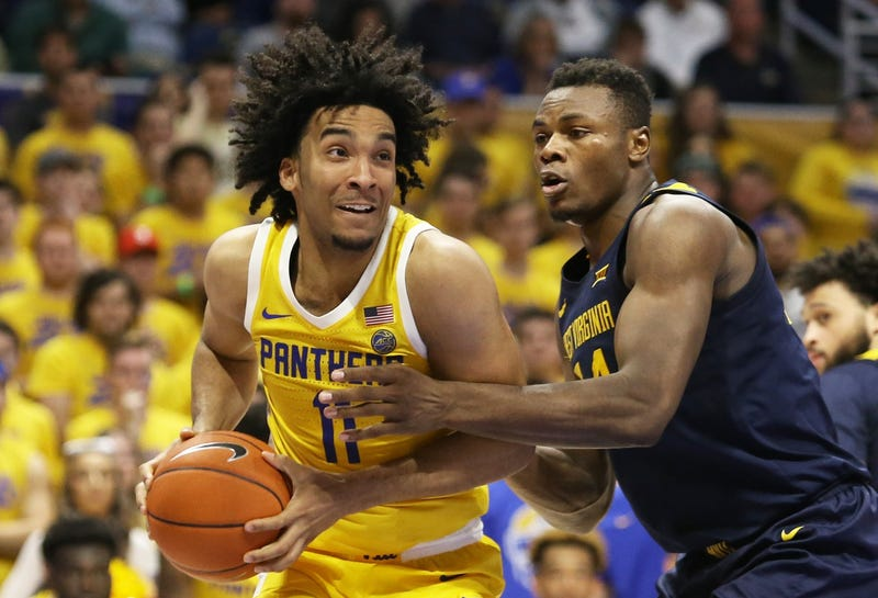 Pittsburgh Panthers guard Justin Champagnie (11) handles the ball against West Virginia Mountaineers forward Oscar Tshiebwe