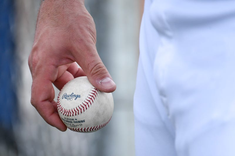 MLB pitcher holding baseball.