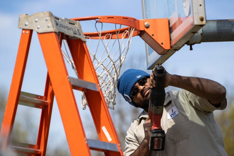JCPS Crew Member Tyrone Fields takes down a basketball hoop at St. Matthews Elementary School.