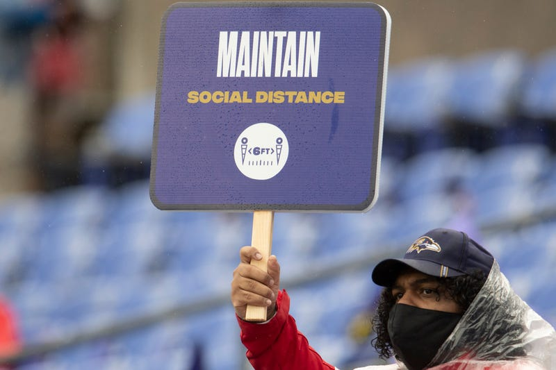 An usher a M&T Bank Stadium reminds fans to 'maintain social distance' during last month's Steelers/Ravens game