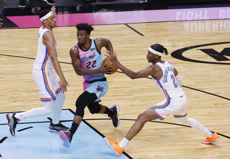 Jimmy Butler is defended by Darius Bazley and guard Shai Gilgeous-Alexander at American Airlines Arena.