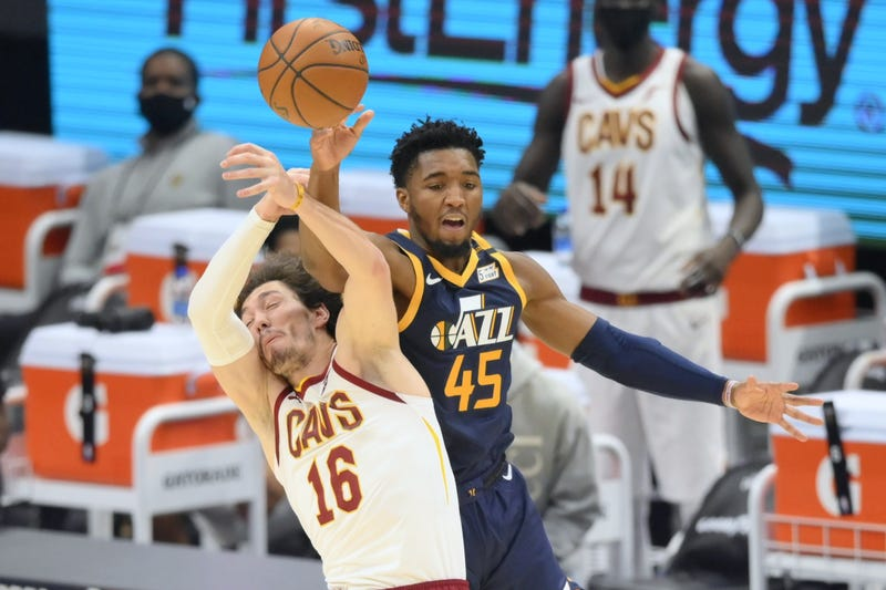 Cleveland Cavaliers forward Cedi Osman (16) and Utah Jazz guard Donovan Mitchell (45) reach for a loose ball in the second quarter at Rocket Mortgage FieldHouse.