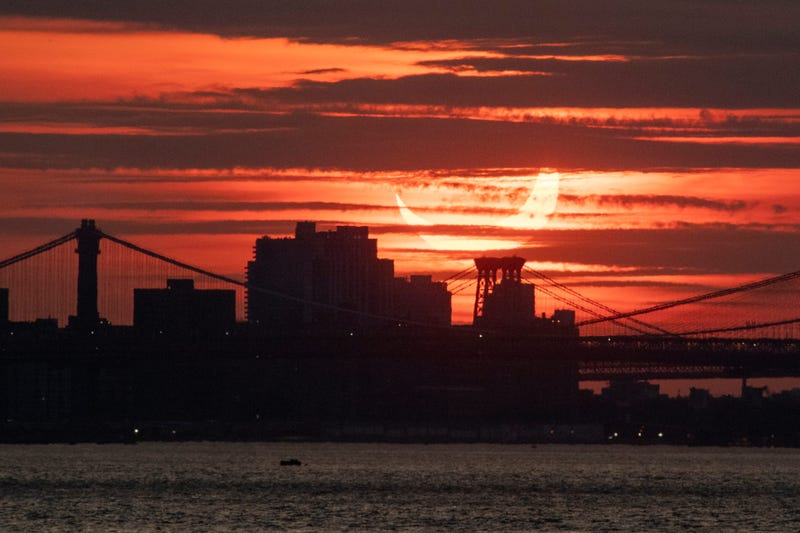 A solar eclipse rises behind the New York City skyline on June 10, 2021