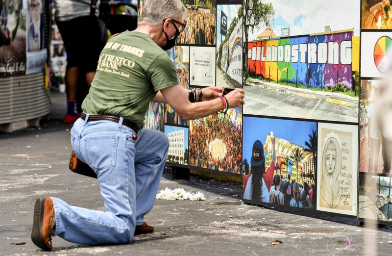 Gino Grossi takes a photo of part of the memorial at Pulse in downtown Orlando