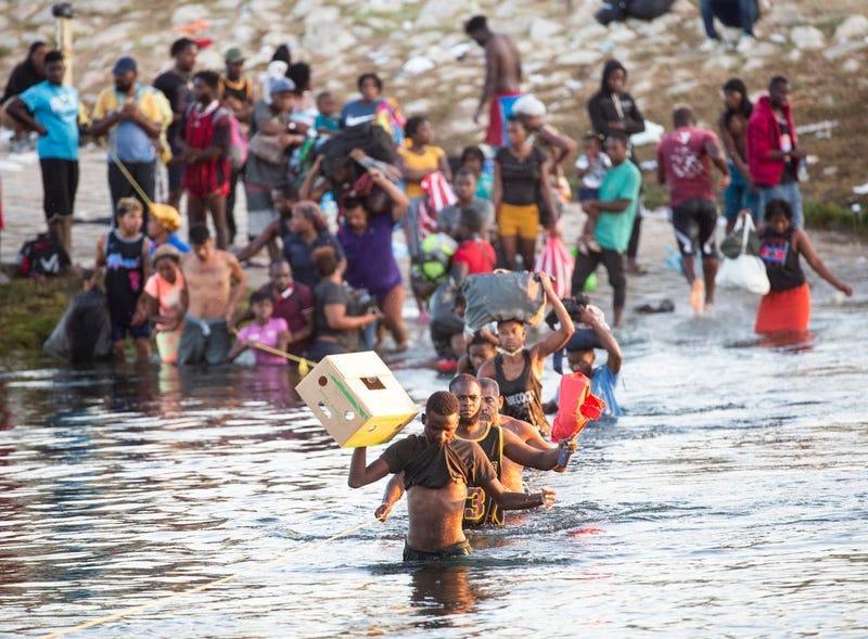 Haitian migrants cross the Rio Grande