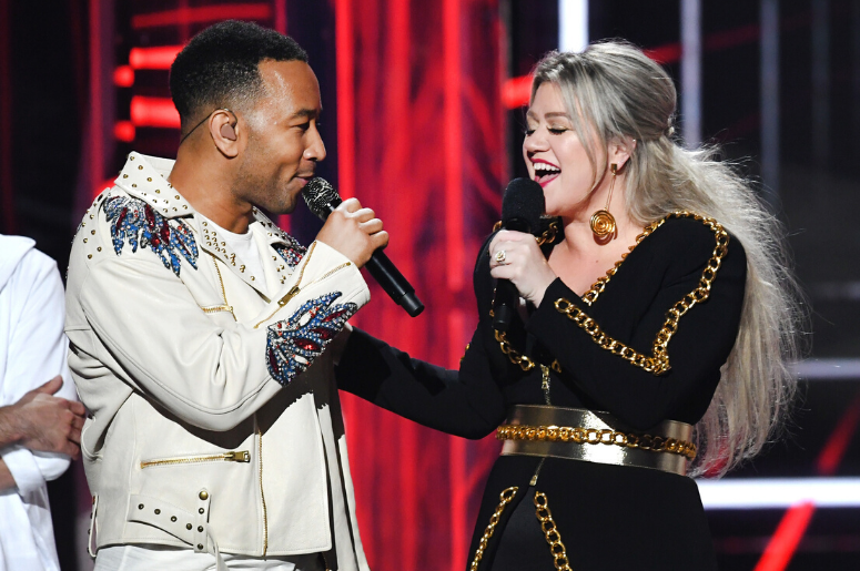 John Legend (L) and host Kelly Clarkson speak onstage during the 2018 Billboard Music Awards
