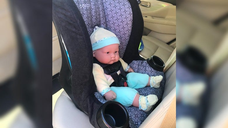 A baby doll in a rear facing car seat in vehicle