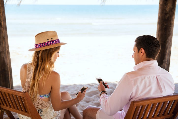 People texting while on vacation at the beach