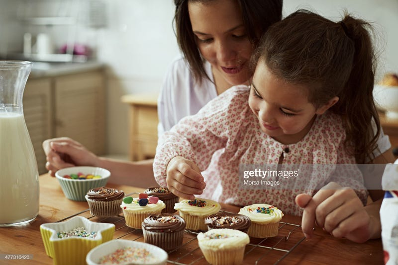 Little girl decorates cupcakes with help from her mom